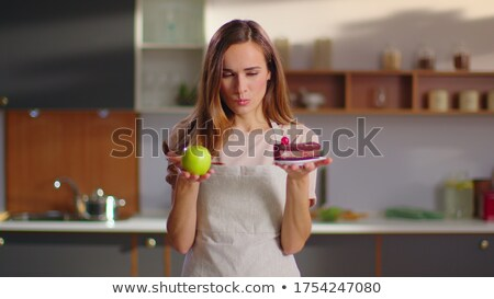 woman making choice between apple and cake stock photo © deandrobot