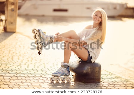 Smiling sporty blonde skater sitting in grass Stock photo © wavebreak_media