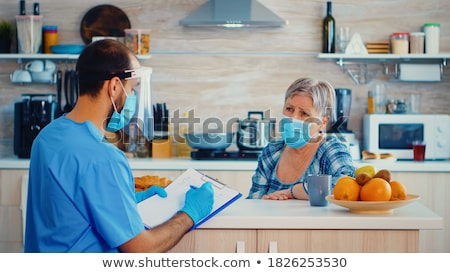 Male doctor writing notes on clipboard paper during medical exam Stock photo © stevanovicigor