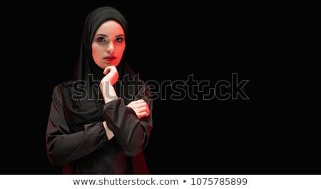Portrait of beautiful serious scared young muslim woman wearing black hijab whispering holding telep Stock photo © Traimak