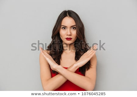 Calm brunette woman in casual clothes showing crossed hands gesture Stock photo © deandrobot