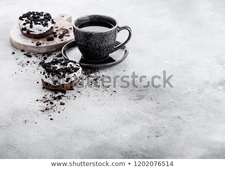 Black coffee cup with saucer and doughnuts with black cookies on stone kitchen table background. Spa stock photo © DenisMArt