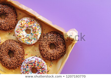 Delicious glazed donuts in box on violet surface stock photo © artsvitlyna