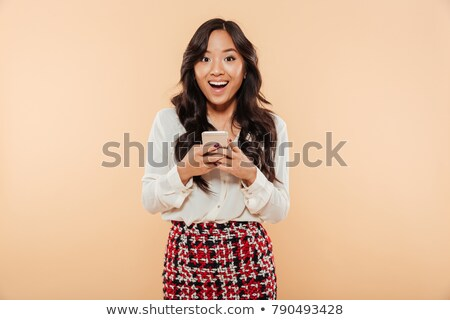 portrait of an excited asian girl isolated over beige stock photo © deandrobot