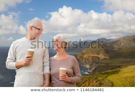 senior couple with coffee cups over big sur coast Stock photo © dolgachov