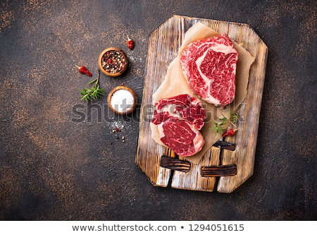 Raw marbled ribeye steak and butchers knife Stock photo © furmanphoto