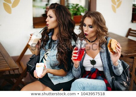 Ladies in cafe drinking lemonade and eating burgers. stock photo © studiolucky