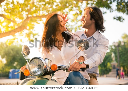 portrait of cheerful couple man and woman riding on scooter tog stock photo © deandrobot