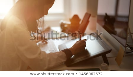 Stock photo: Young woman designer sitting in office working using mobile phone at night.