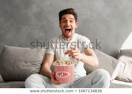 Feliz soltero sesión sofá gris apartamento Foto stock © deandrobot