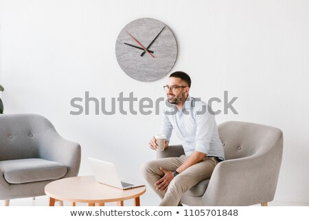 Image of diligent office man 30s in white shirt sitting in armch Stock photo © deandrobot