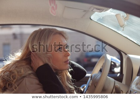 Dangerous young woman driver fluffing up her hair Stock photo © Giulio_Fornasar