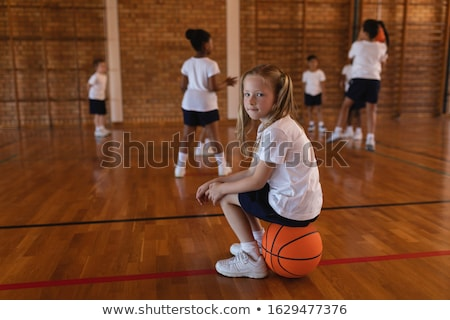 Side view of schoolgirl sitting on basketball and looking at camera at basketball court in school Stock photo © wavebreak_media