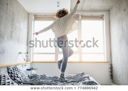 Mooie vrouw springen bed heldere slaapkamer interieur Stockfoto © chocolatehouse