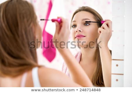 Woman wearing hair rollers applying make-up Stock photo © photography33