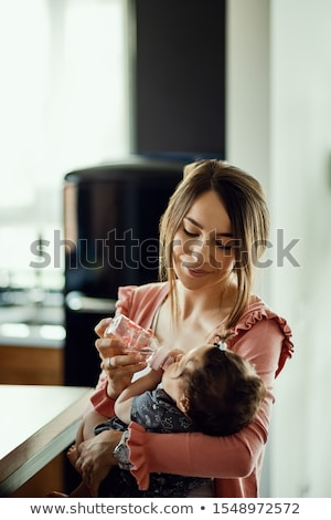 Girl giving baby her bottle Stock photo © photography33