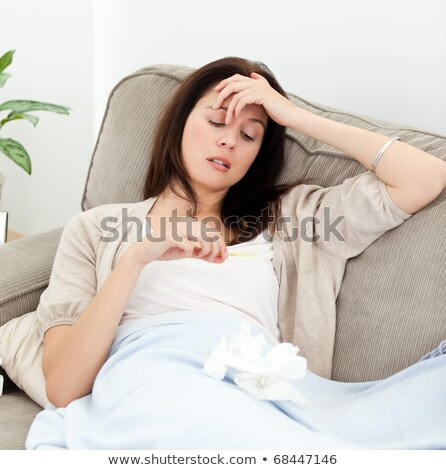 Sick woman looking at a clinical thermometer  Stock photo © dacasdo