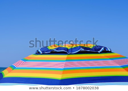 A beach under the sky with a rainbow and a bright sun Stock photo © bluering
