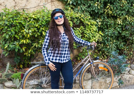 Smiling woman in sunglasses walking with bicycle and takeaway coffee Stock photo © deandrobot