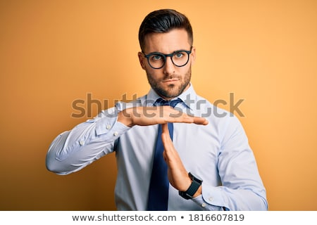 Angry bearded businessman in glasses standing with hands on hips Stock photo © deandrobot