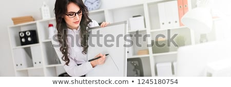 A beautiful young girl stands near an office desk and draws a magnetic marker on the magnetic board. Stock photo © Traimak