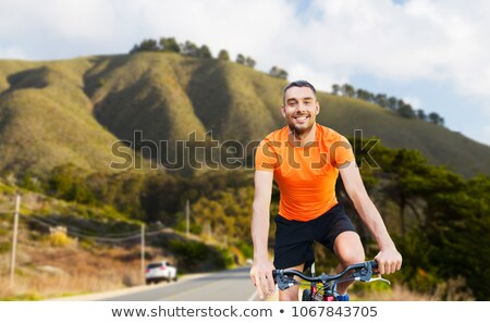 happy young man riding bicycle over big sur hills Stock photo © dolgachov