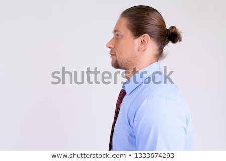 Profile closeup of handsome bearded man 30s with tied hair in wh Stock photo © deandrobot