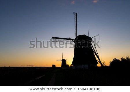 silhouette of windmill on farmland against orange yellow sky stock photo © lovleah