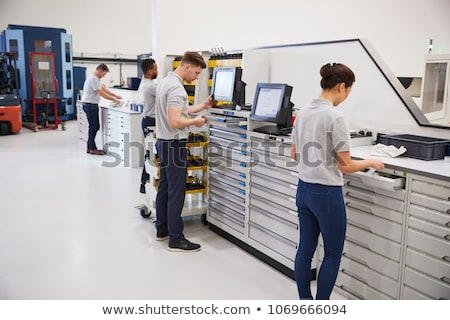 Woman worker operating a machine tool in metal workshop or factory Stock photo © Kzenon