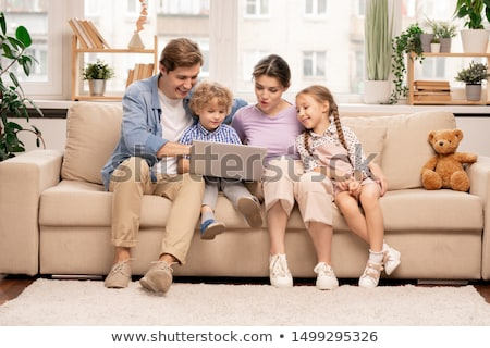 Young family with laptop surfing in the net while choosing movie or cartoons Stock photo © pressmaster