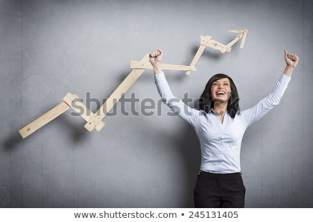Overjoyed businesswoman in front of ascending business graph. Stock photo © lichtmeister