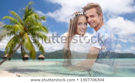 hippie couple fading over exotic beach background Stock photo © dolgachov