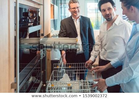 couple checking dishwasher of new kitchen in the showroom stock photo © kzenon