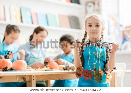 Pretty blonde schoolgirl holding stick with several halloween leaves on threads Stock photo © pressmaster