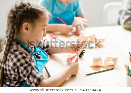 cute girl with scissors sitting by table and cutting paper halloween symbols stock photo © pressmaster