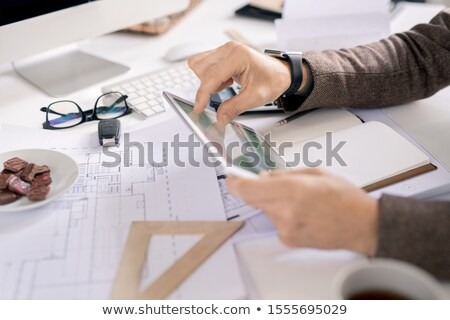 Hands of contemporary engineer with touchpad looking through electronic data Stock photo © pressmaster