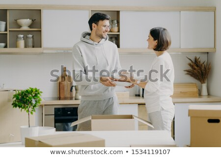 Positive young husband and wife unpack personal belongings in kitchen, carry plates, look gladfully  Stock photo © vkstudio