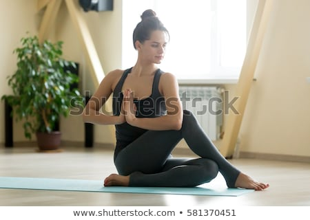 Young beautiful woman doing yoga asana half lord of the fishes pose on dark room Stock photo © GVS