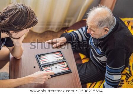 Senior man and his grandson play backgammon Stock photo © galitskaya
