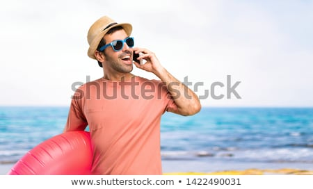 Stock photo: man on vacation talking on his cell phone