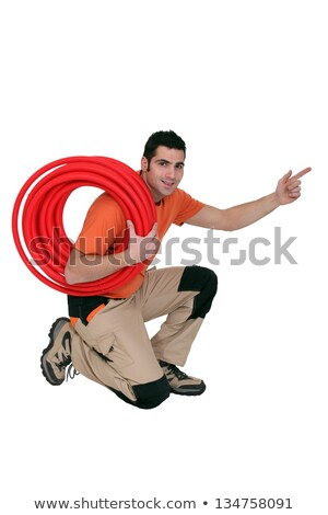 Plumber with coiled pipe pointing in to the distance Stock photo © photography33