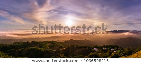 Layers of clouds in the evening sky above rolling hills landscap Stock photo © inarts