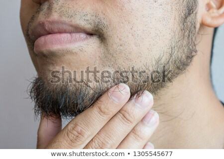young fashion man touches lower lip Stock photo © feedough