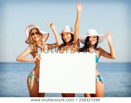group of smiling women with blank board on beach stock photo © dolgachov