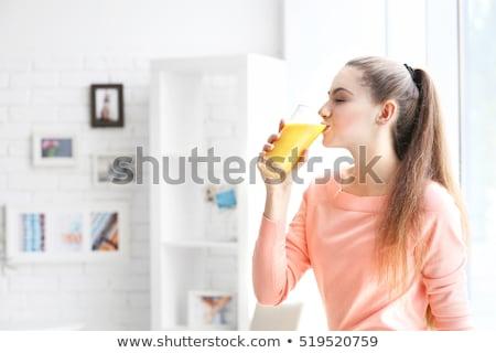encantador · mulher · potável · suco · de · laranja · sorridente · câmera - foto stock © d13