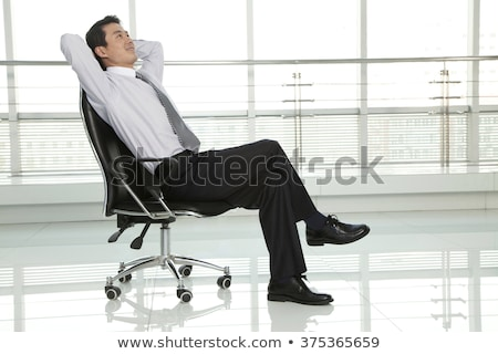 Confident businessman sitting at the office chair and looking away at office Stock photo © deandrobot
