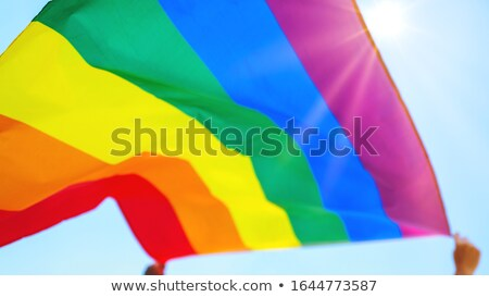 hands holding rainbow flags over sky background Stock photo © dolgachov