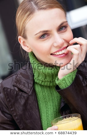 Stock photo: young smiling woman with hand under chin holding a glass of orange juice and looking at camera
