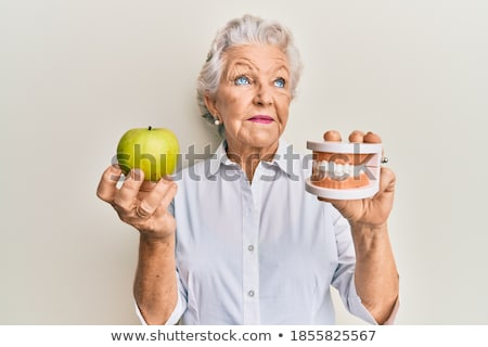 side view portrait of a woman holding apple stock photo © deandrobot