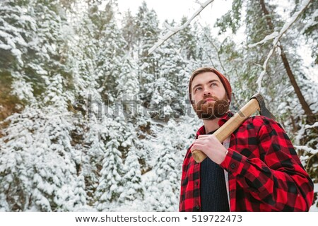 bearded man with axe walking in mountain winter forest stock photo © deandrobot
